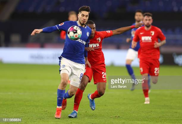 Suat Serdar of FC Schalke 04 battles for possession with Carlos Gruezo of FC Augsburg during the Bundesliga match between FC Schalke 04 and FC...