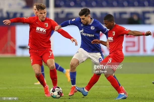 Suat Serdar of FC Schalke 04 battles for possession with Florian Niederlechner and Carlos Gruezo of FC Augsburg during the Bundesliga match between...
