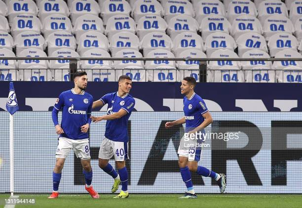 Suat Serdar of FC Schalke 04 celebrates with Can Bozdogan and Amine Harit after scoring their side's first goal during the Bundesliga match between...