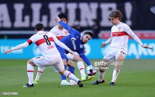 Suat Serdar of FC Schalke 04 is challenged by Gonzalo Castro, Wataru Endo and Borna Sosa of VfB Stuttgart during the Bundesliga match between VfB...