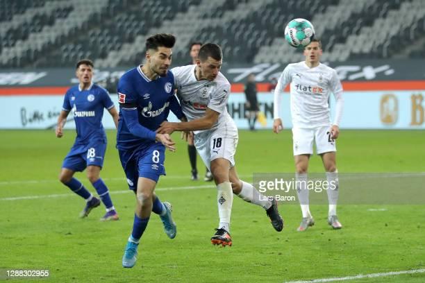 Suat Serdar of FC Schalke 04 is challenged by Stefan Lainer of Borussia Monchengladbach during the Bundesliga match between Borussia Moenchengladbach...