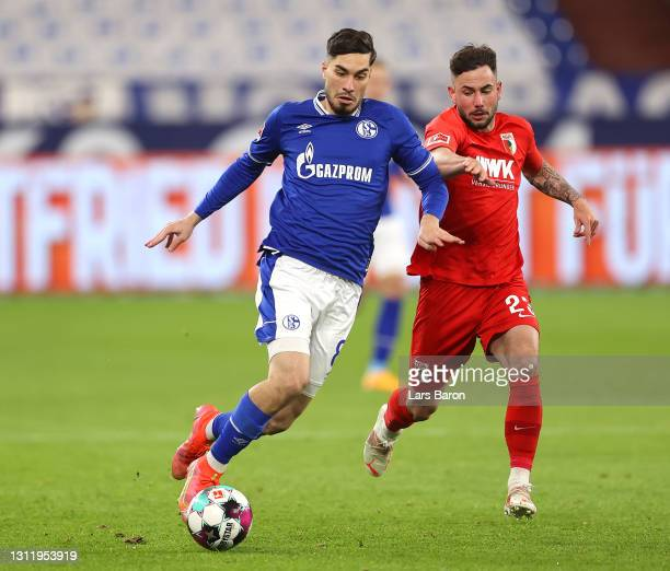 Suat Serdar of FC Schalke 04 runs with the ball whilst under pressure from Marco Richter of FC Augsburg during the Bundesliga match between FC...