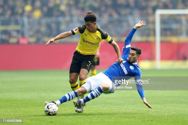 Suat Serdar of FC Schalke 04 tackles Jadon Sancho of Borussia Dortmund during the Bundesliga match between Borussia Dortmund and FC Schalke 04 at...