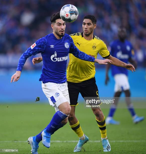 Suat Serdar of FC Schalke shoots is challenged by Achraf Hakimi of Borussia Dortmund during the Bundesliga match between FC Schalke 04 and Borussia...