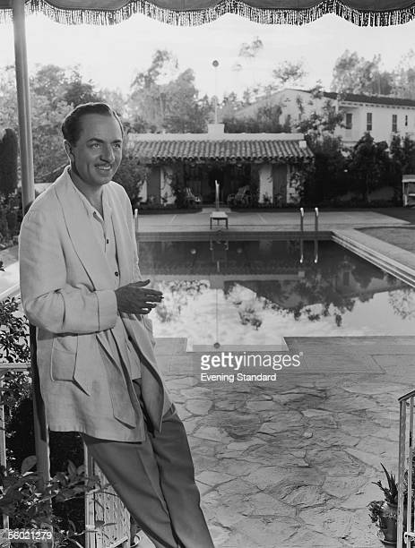 Suave American actor William Powell relaxes fullyclothed by a swimming pool 1939