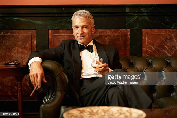 suave man in a cigar lounge - dinner jacket stock pictures, royalty-free photos & images