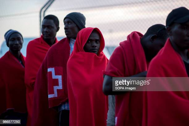 PORT MOTRIL GRANADA SPAIN Sub Saharan migrants covered with red blankets waiting to be registered and assisted by Red Cross at Motril port 58 people...