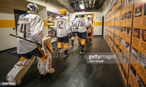 K Subban Mike Fisher and Juuse Saros of the Nashville Predators walk to the ice for warmups wearing their social media tags prior to an NHL game...