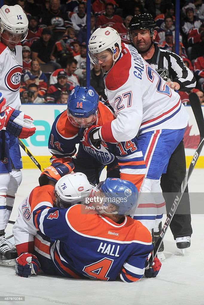 P.K. Subban #76 of the Montreal Canadiens and Taylor Hall #4 of the Edmonton Oilers grapple on the ice on October 27, 2014 at Rexall Place in Edmonton, Alberta, Canada.