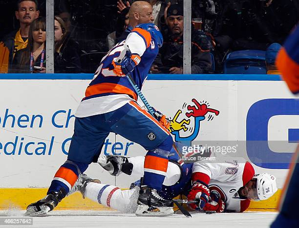 K Subban of the Montreal Canadiens is hit into the boards by Casey Cizikas of the New York Islanders during the first period at the Nassau Veterans...