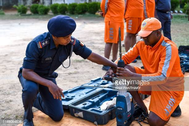 SubInspector at India's 6th National Disaster Response Force Rakeshkumar Dohare looks on as a NDRF personnel checks a cementconcrete machine at a...