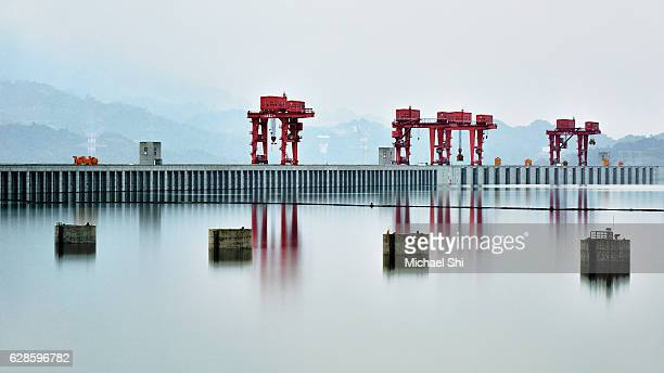 a sublime landscape expansive view of china's three gorges dam on the yangtze river in diffused soft light with reflections of the dam in the water showcasing the zen-like tranquility. - dam china stock pictures, royalty-free photos & images