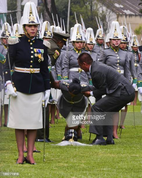 A subliutenant is assisted after fainting during a ceremony at the Police School General Santander in Bogota during the 121st anniversary of the...