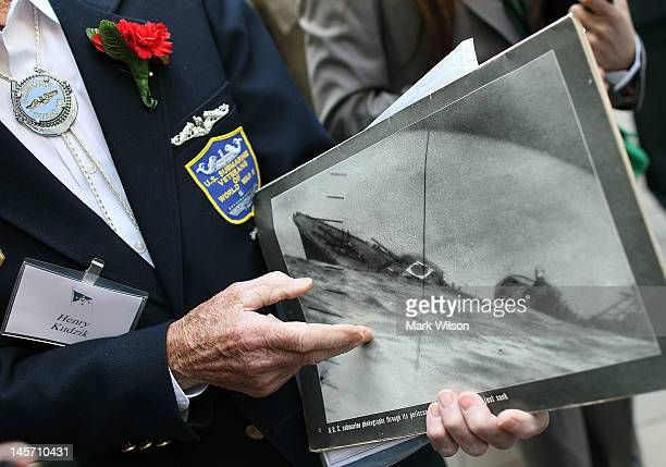 WWII submarine veteran Henry Kudzik sits with other veterans while holding a Life magazine picture of a Japanese ship sinking after being torpedoed...