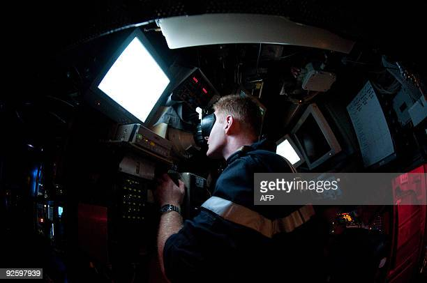 A submariner of French nuclear submarine 'Casabianca' looks through periscope on October 19 off Toulon during a practice session AFP PHOTO / MARTIN...