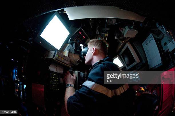 A submariner of French SNA class submarine 'Casabianca' looks through the periscope on October 19 off Toulon during a training mission Un...