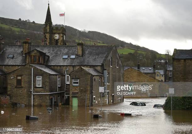 Submerged cars and floating wheelie bins are pictured in a flooded street in Mytholmroyd northern England on February 9 after the River Calder burst...