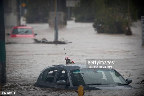 Submerged cars sit abandoned in a flooded carpark in Toombul in Queensland on March 30 2017 Torrential rain hampered relief efforts after powerful...