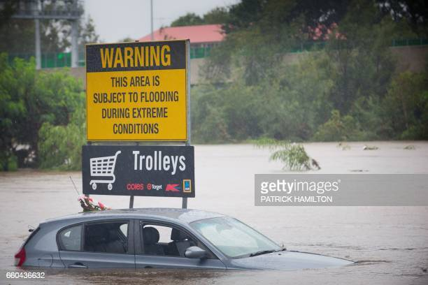 Submerged cars sit in a flooded carpark in Toombul in Queensland on March 30 2017 Torrential rain hampered relief efforts after powerful cyclone...