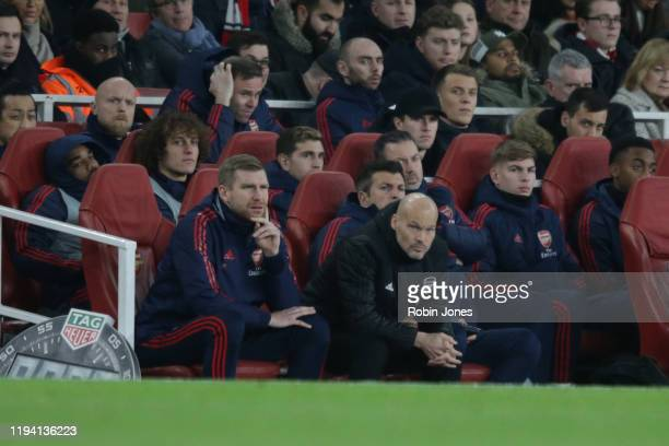 Subs Alexandre Lacazette and David Luiz sit behind Per Mertesacker and Fredrik Ljungberg of Arsenal during the Premier League match between Arsenal...