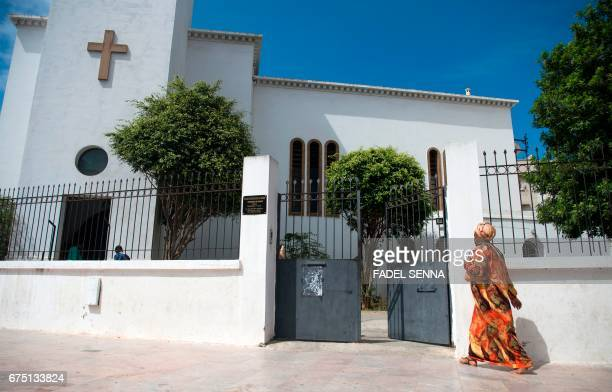 A SubSaharan Christian woman arrives for a mass at a Protestant church in the Moroccan capital Rabat on April 30 2017 Moroccans who secretly...