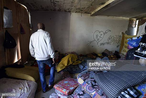 A SubSaharan man makes his way through mattresses on the floor at a makeshift building where he lives with other fellow migrants in impoverished...