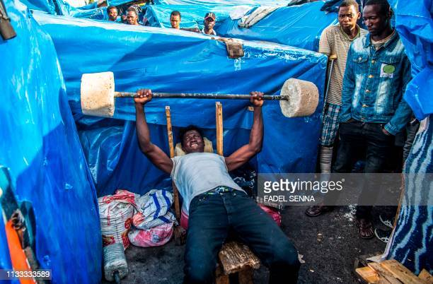 TOPSHOT A subSaharan migrant lifts weights with a makeshift barbell between makeshift tents in the Oulad Ziane migrant camp in Casablanca on March 27...