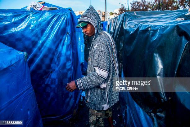 TOPSHOT A subSaharan migrant walks between makeshift tents in the Oulad Ziane migrant camp in Casablanca on March 27 2019 Migrants at a squalid camp...