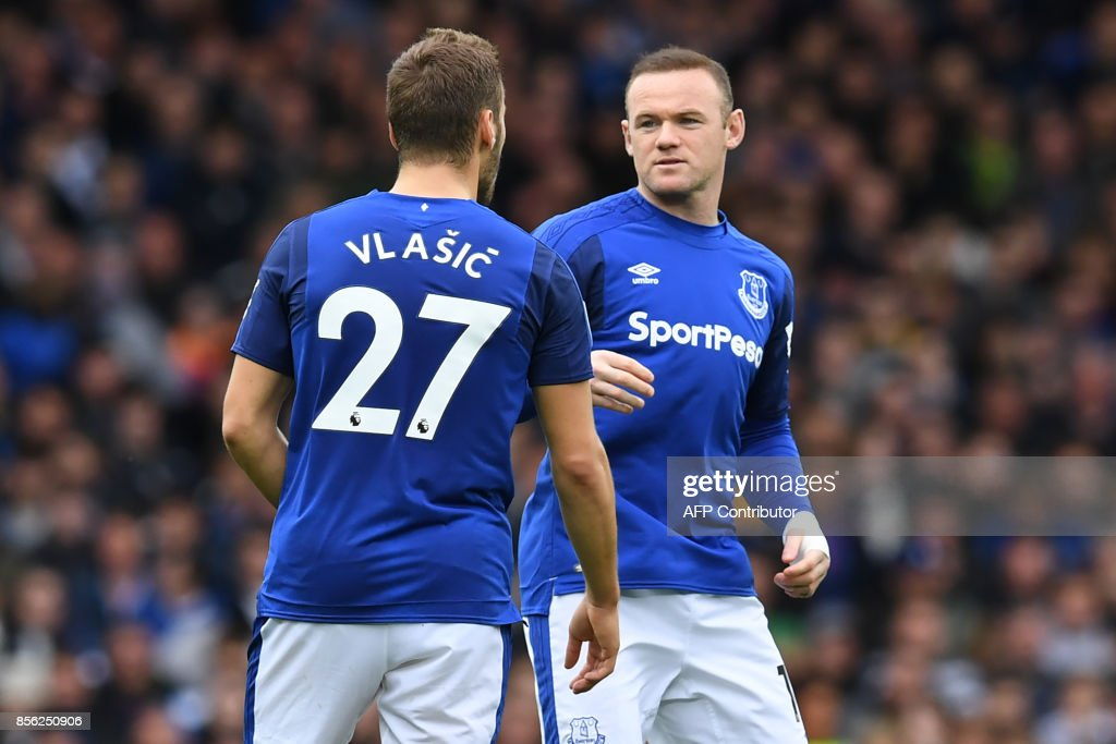 Substitute Everton's English striker Wayne Rooney (R) speaks with Everton's Croatian striker Nikola Vlasic (L) during the English Premier League football match between Everton and Burnley at Goodison Park in Liverpool, north west England on October 1, 2017. / AFP PHOTO / Paul ELLIS / RESTRICTED TO EDITORIAL USE. No use with unauthorized audio, video, data, fixture lists, club/league logos or 'live' services. Online in-match use limited to 75 images, no video emulation. No use in betting, games or single club/league/player publications. /