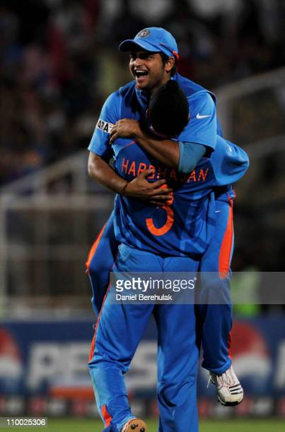 Substitute fieldsman Suresh Raina of India, celebrates with team mate Harbhajan Singh, after taking the catch to dismiss Johan Both of South Africa...