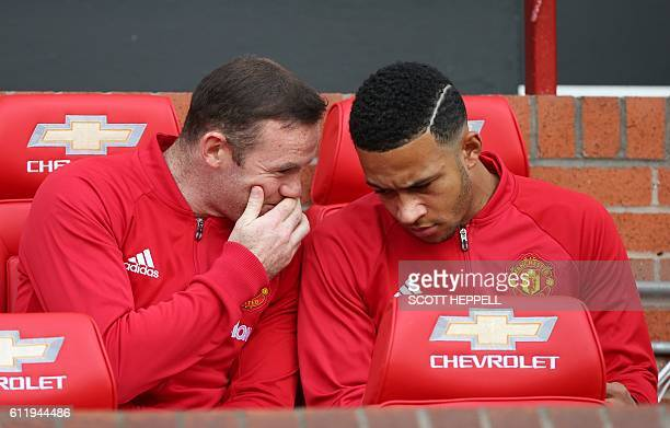 Substitute Manchester United's English striker Wayne Rooney talks to Manchester United's Dutch midfielder Memphis Depay on the bench ahead of the...