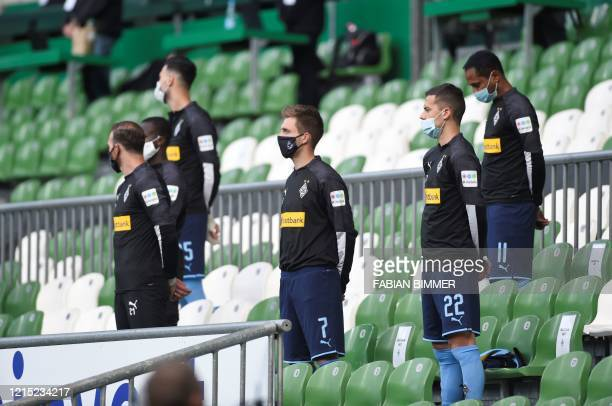 Substitute players observe a minute of silence for the victims of the coronavirus COVID-19 pandemic prior to the German first division Bundesliga...