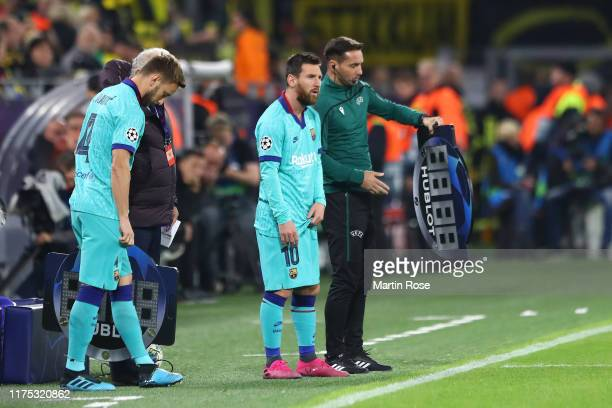 Substitutes Lionel Messi and Ivan Rakitic of FC Barcelona look on from the touchline during the UEFA Champions League group F match between Borussia...