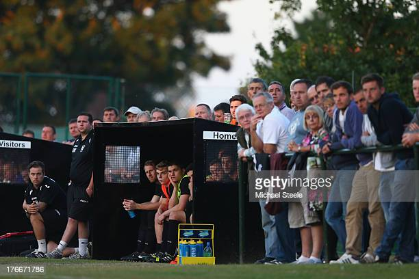 Substitutes of Alresford Town look on alongside supporters during the FA Cup Extra Preliminary Round match between Alresford Town and Winchester City...