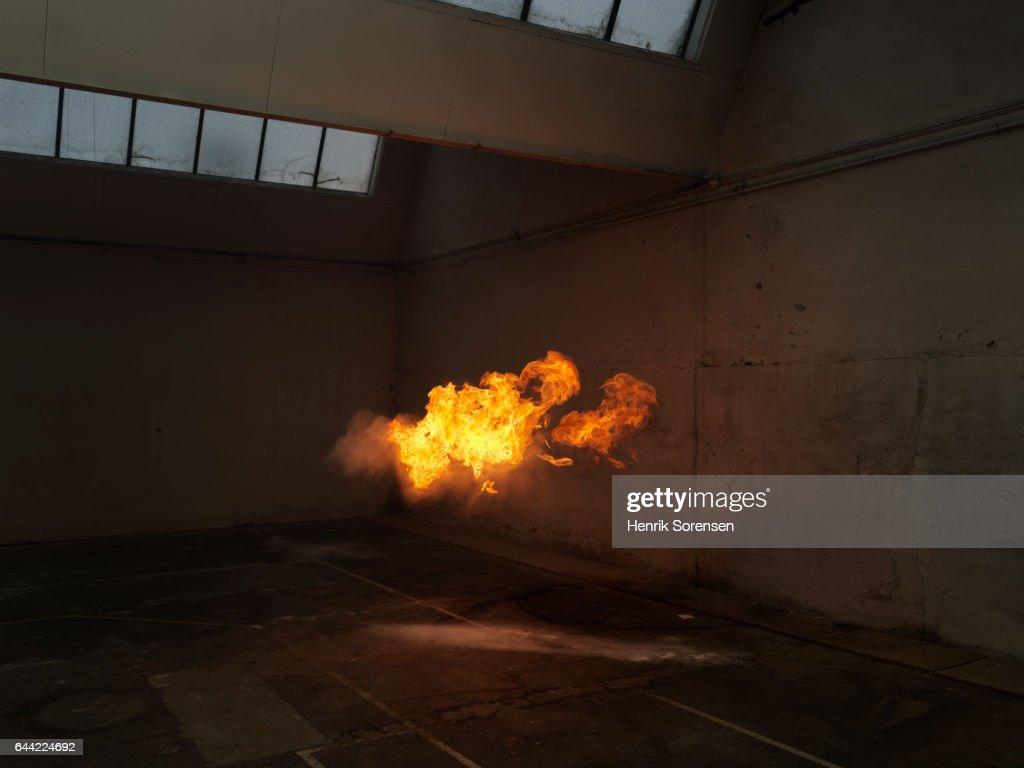 Subtle flame inside old warehouse : Stock Photo