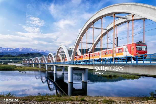 suburb passenger train drive through the viaduct towards the tatra mountains - poland stock pictures, royalty-free photos & images