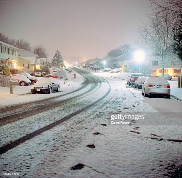 Suburb road with snow fallen, a few inches sticking to the pavement, with footsteps as well as car tracks through it. The lights on the street are...
