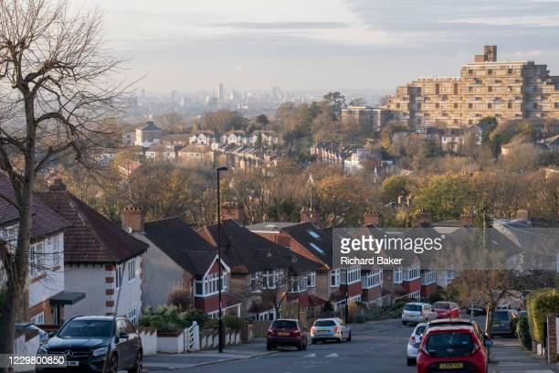 Suburban homes, flats and parked cars with a cityscape looking north from Horniman Hill towards the prominent residential complex of Dawson Heights...