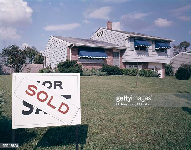 Suburban House With Blue Awnings And A Sold Sign On Front Lawn Real Estate