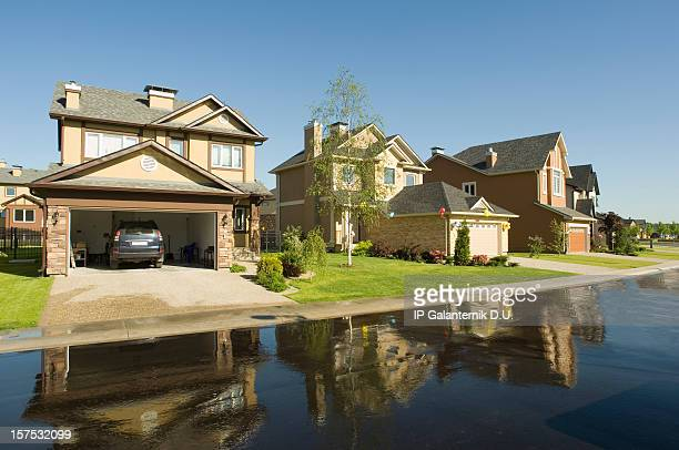 suburban houses reflected in wet driveway. - borough district type stock pictures, royalty-free photos & images