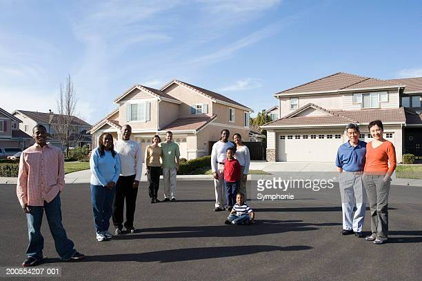 Suburban neighbours posing together in street, portrait
