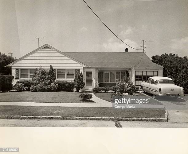Suburban tract house with vintage car in drive