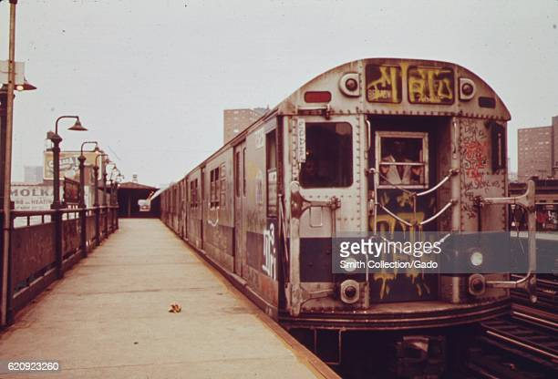 A subway car marked with extensive graffiti waits at a station platform New York City New York 1972 Image courtesy National Archives