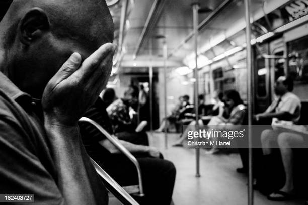 CONTENT] A subway commuter burrowing his face in his hands on the subway Ctrain New York CIty