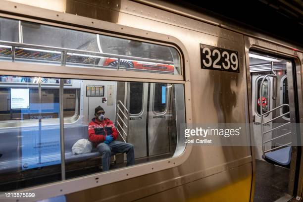 subway commuter wearing respirator mask in new york city - new york coronavirus stock pictures, royalty-free photos & images