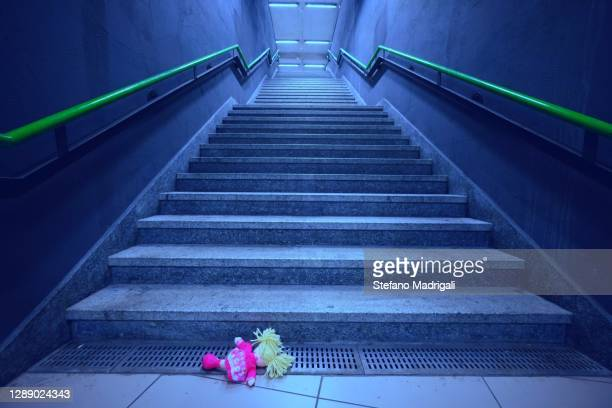 subway corridor and stairway to the top with abandoned doll, concept of abandonment and uncertainty at the time of the lockdown - extremism stock pictures, royalty-free photos & images