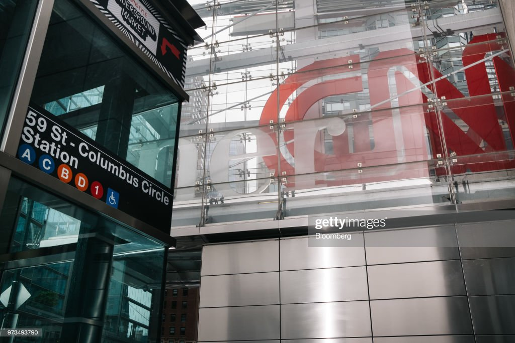 A subway entrance stands in front of a building complex displaying Time Warner Inc. brand CNN television network signage in New York, U.S., on Wednesday, June 13, 2018. AT&T Inc.'s sweeping court victory allowing its takeover of Time Warner Inc. delivers a sharp setback to the Justice Department's new approach to policing mergers under President Donald Trump and promises to spark a merger wave across industries. Photographer: Christopher Lee/Bloomberg via Getty Images
