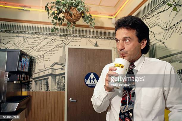 Subway founder Fred DeLuca drinks a soda during his visit to an Anaheim Subway
