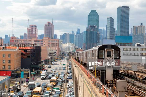 subway train approaching  elevated subway station in queens, new york - queens new york city stock pictures, royalty-free photos & images