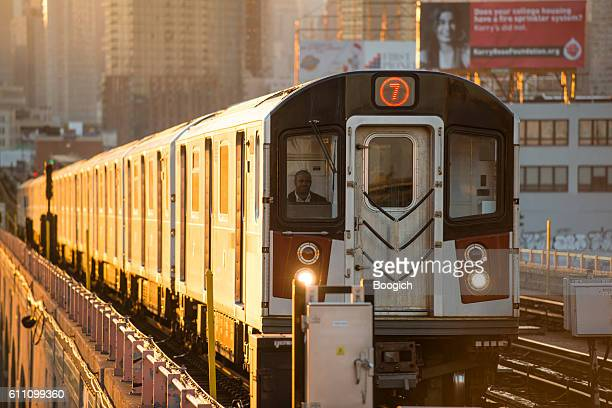 nyc subway train drives toward queens during rush hour sunset - queens new york city stock pictures, royalty-free photos & images
